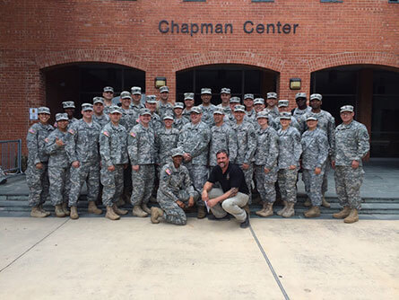 A group, all wearing camouflage, standing in front of a brick building named Chapman Center