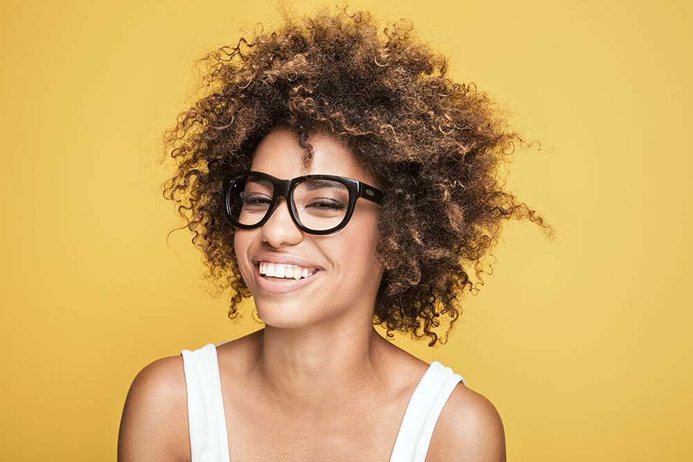 A woman with a wide smile, curly hair, and wearing dark glasses, sitting with an orange background