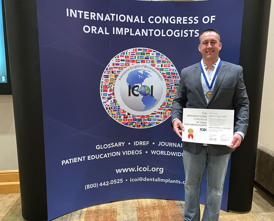 Dr. Croupi, holding an award from the International Congress of Oral Implantologists