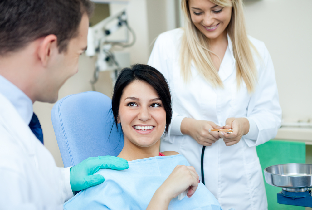 A patient sitting in the dental chai smiling at dentist