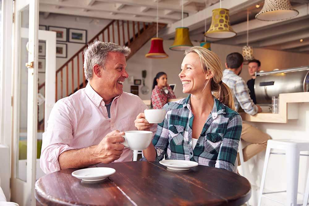 A man and woman laughing while on a coffee date
