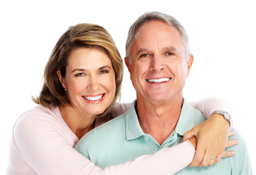 A woman with her arms over a man's shoulders while they're smiling