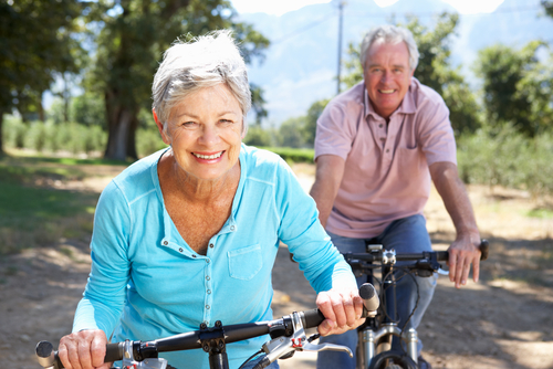 A man and woman smiling and riding bikes on a trail